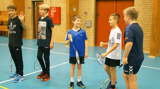 Smilende drenge med badmintonketchere