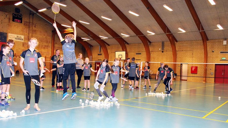 Jublende unge træner med fjerbolde